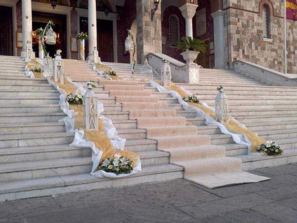 In questa foto i gradini di una chiesa decorati con un tappeto colore avorio, lanterne, tulle colore avorio, drappi di stoffa bianca e composizioni di fiori abbinati