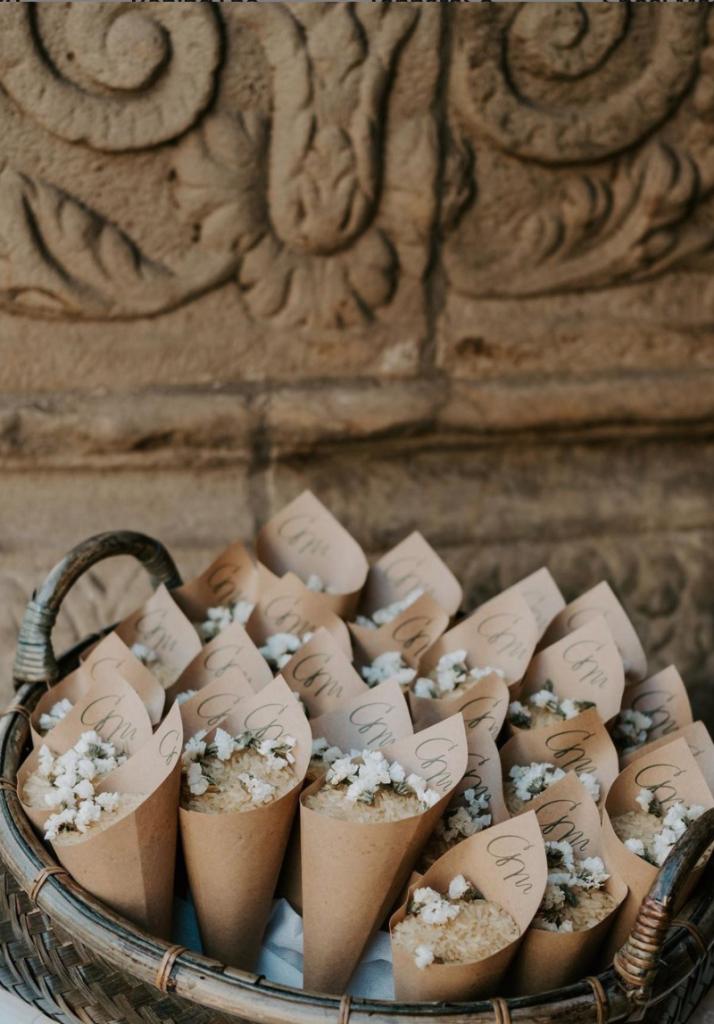 In questa foto conetti di riso e fiori di campo bianchi in carta grezza inseriti in una cesta di vimini poggiata davanti alla colonna di una chiesa