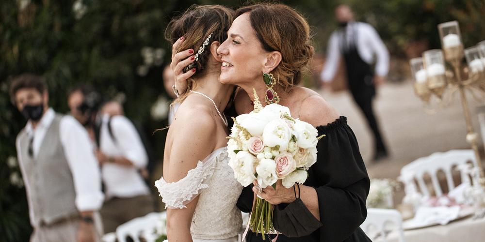 In questa foto la Wedding Planner di Palermo Antonella Candido abbraccia una sposa prima del ricevimento sulla terrazza del Castello di Solanto. Antonella le tiene una mano dietro la testa tenendole il bouquet di rose rosa
