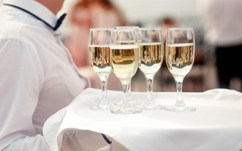 In questa foto un vassoio con flute di champagne tenuto da un cameriere