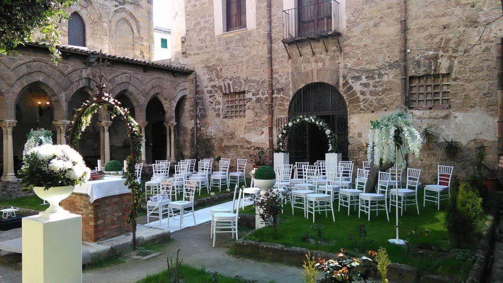In questa foto il chiostro della Magione a Palermo decorato per un matrimonio all'aperto con alzatine di fiori bianchi, archi di fiori, sedie bianche e un tappeto bianco