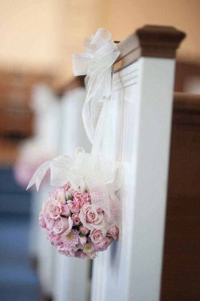 In questa foto una sfera di boccioli di rose rosa legata al banco bianco di una chiesa con un nastro largo di organza