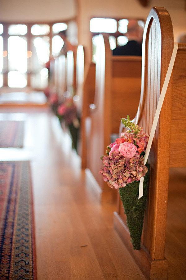 In questa foto in primo piano un cono di muschio verde ripieno di fiori rosa e verdi, legato al banco di una chiesa con un nastro sottile di seta. Fuori fuori, dietro, si intravedono altri coni dello stesso tipo. Lungo il bordo sinistro della foto ci sono dei tappeti