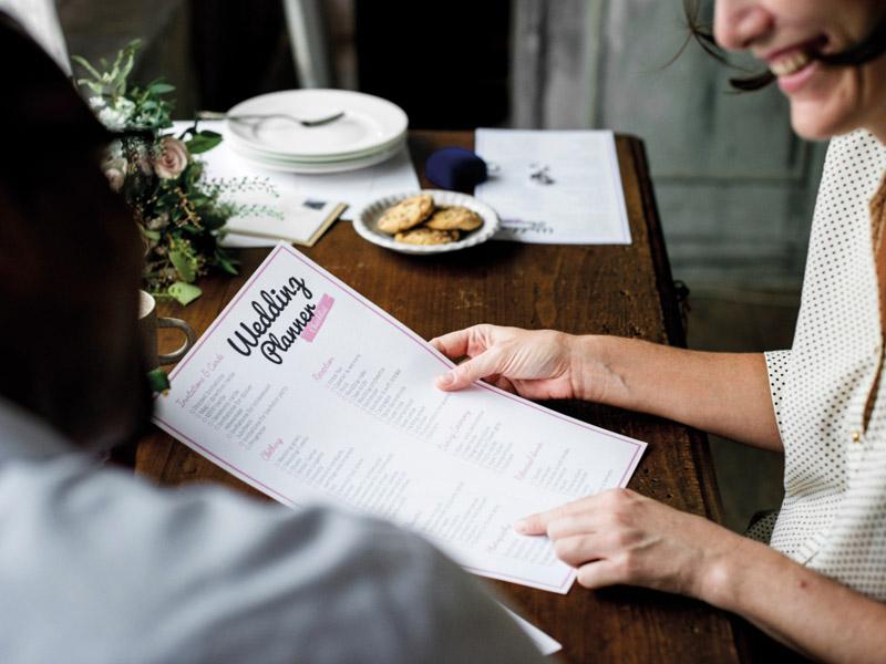 In questa foto sedute ad una scrivania una ragazza di spalle ascolta una wedding planner che le mostra il piano operativo del matrimonio