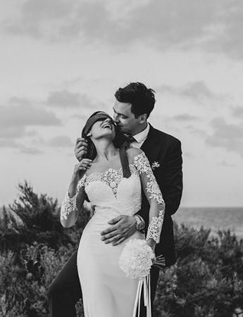 Una romantica foto in bianco e nero ritrae coppia di sposi in riva al mare