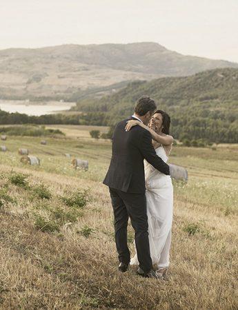 Sposi abbracciati in un campo