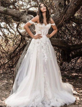 In questa foto un abito da sposa ampio con scollo a barchetta in pizzo e tulle e ricami floreali