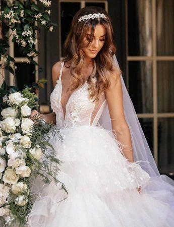 In questa foto un abito da sposa a balze e scollo a V semitrasparente di Millanova. la sposa indossa un velo con coroncina