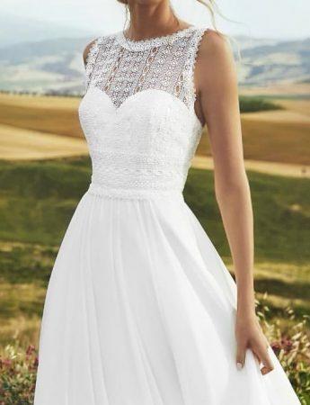 In questa foto un abito da sposa scivolato in stile boho chic con corpetto girocollo in pizzo trasparente. Sotto si intravede anche uno scollo a cuore