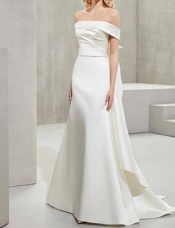 In questa foto un abito da sposa mezza sirena in mikado con scollo omerale