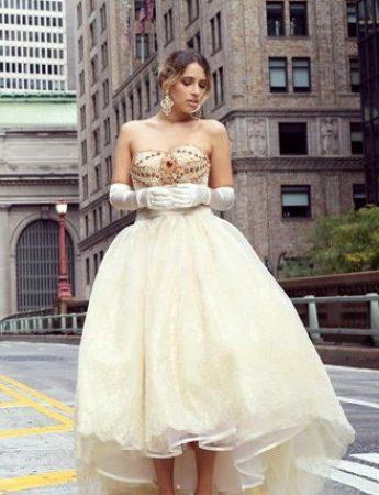 In questa foto un abito corto in tulle con coda colore champagne con guanti abbinati