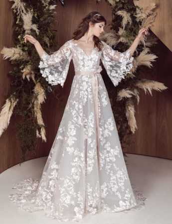 In questa foto un abito da sposa ampio con ricami florelai, maniche ampie e cinturino in seta rosa