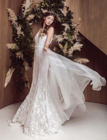 In questa foto un abito da sposa a sirena con ricami floreali su busto e orlo inferiore con sovragonna trasparente
