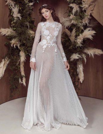 In questa foto un abito da sposa in rete trasparente con ramage floreali sul busto firmato da Marco Strano