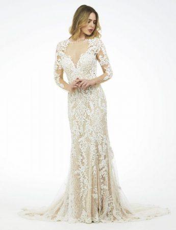 In questa foto un abito da sposa a sirena in pizzo con maniche di Mariella Gennarino