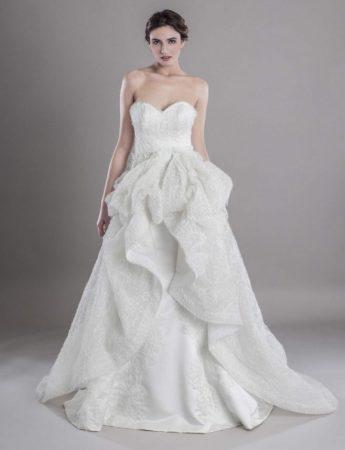 In questa foto un abito da sposa ampio con scollo a cuore e maxi rouches su tessuto reticolato