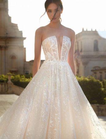 In questa foto un abito da sposa ampio con corpetto senza spalline e scollo a V di Nicole Couture