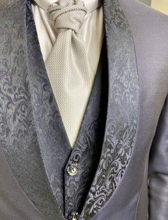 In questa foto un dettaglio di un bellissimo abito da sposo con decori damasco dai toni del blu con accessori grigio perla