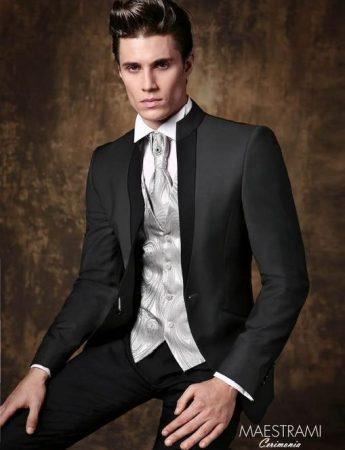 In questa foto un abito da sposo dai toni del nero arricchito da un gilet grigio perla disponibile da Sposo Trend