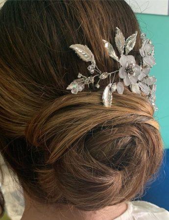 In questa foto un'acconciatura da sposa con chignon e accessorio per capelli floreale