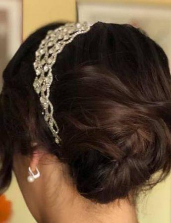 In questa foto un'acconciatura da sposa con chignon e cerchietto gioiello