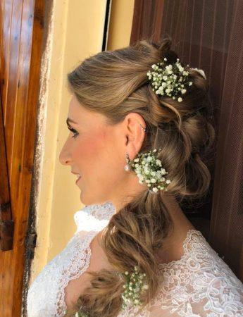 In questa foto un'acconciatura da sposa con treccia e fiorellini sulle lunghezze
