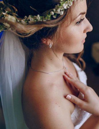 In questa foto un'acconciatura sposa con piccoli inserti floreali e velo
