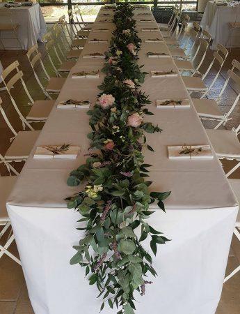 Un tavolo allestito con un runner di foglie e fiori in stile country chic