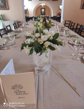 Il particola di un centro tavola con fiori bianchi e verdi