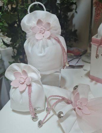 In questa foto eleganti sacchetti di confetti bianchi a cui è abbinato un fiore di ceramica rosa cipria