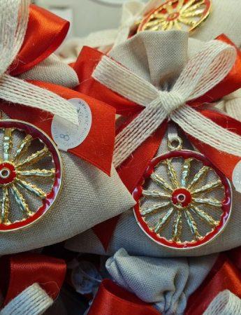 In questo scatto dei particolari sacchettini di confetti arricchiti con un particolare ciondolo a forma di ruota di carretto siciliano