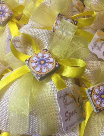 In questa foto dei sacchetti per confetti dai toni del giallo arricchiti da una mini maiolica