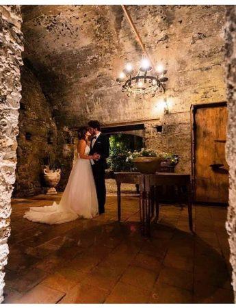 In questa foto due sposi posano in un ambiente dal gusto rustico della Casa del Grecale