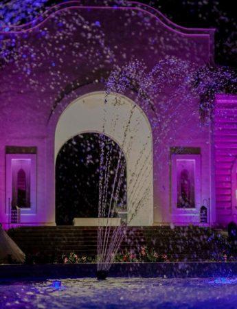 Sposi fotografati davanti a una fontana, tra giochi di acqua e luci