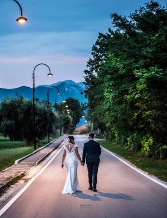 Una coppia di sposi che passeggia tra i viali di una villa,all'imbrunire