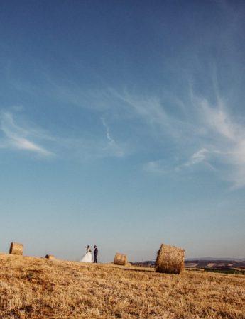 Due sposi fotografati in uno scenario bucolico, tra campi e balle di fieno
