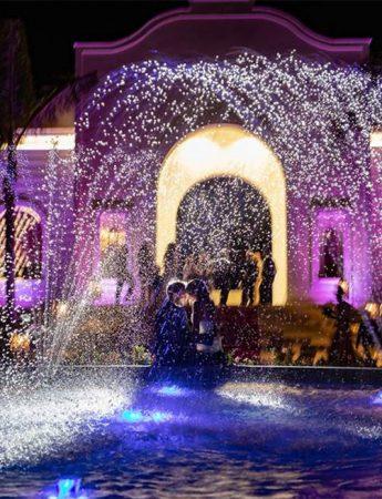 Una coppia di sposi fotografati davanti a una fontana