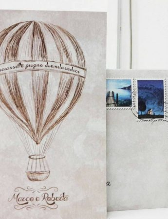 Un invito ispirato al mondo dei viaggi, al centro stampato una mongolfiera disegnata a mano