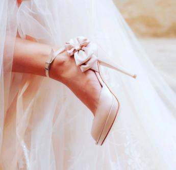 In questa foto scarpe da sposa con fiocco laterale e cinturino alla caviglia