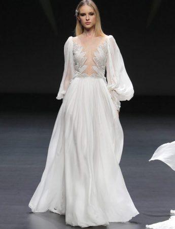 In questa foto una modella indossa un abito da sposa Pronovias con leggere maniche a palloncino