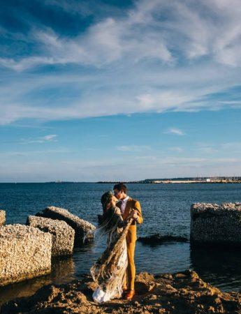 Una coppia di sposi fotografata in riva al mare