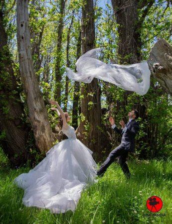 In questa foto una coppia di sposi e il particolare del velo volante sopra le loro teste