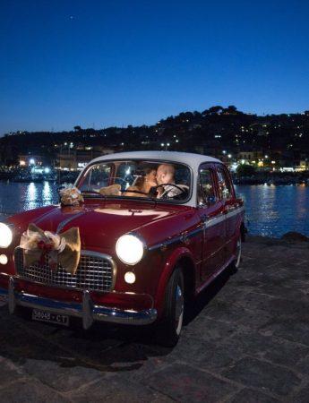 Una coppia di sposi in un'auto rossa stile retrò