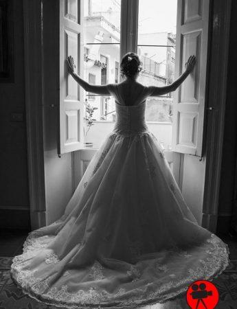 In questa foto in bianco e nero una sposa di spalle davanti a una finestra