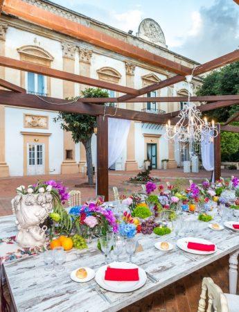 In questa foto una mise en place in stile Boho Chic nei colori fuxia, arancione, azzurro e rosso. Sullo sfondo Villa Boscogrande a Palermo