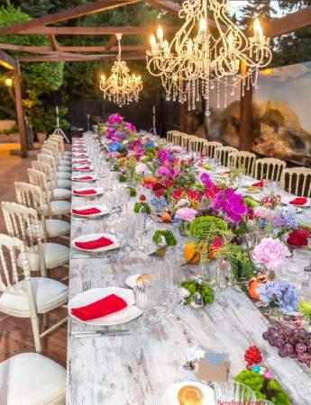 In questa foto una mise en place in stile Boho Chic nei colori fuxia, arancione, azzurro e rosso realizzato sulla terrazza esterna di Villa Boscogrande a Palermo