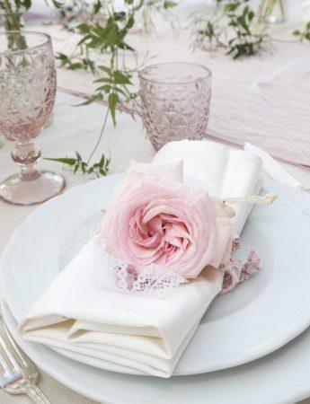 In questa foto una mise en place elegante nei colori del rosa e del bianco. Il fermatovagliolo è realizzato con una rosa in coordinato