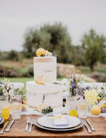 In questa foto una mise en place Boho Chic nei colori del bianco e del giallo visto frontalmente. Un tavolo in legno è decorato con un runner bianco, piatti e bicchieri bianchi e gialli. Al centro è presente una torta nuziale Naked Cake