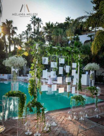 In questa foto un tableau de mariage allestito a bordo piscina. Le card sono appese ad una cornice trasparente decorata con rami di foglie rampicanti e attorno sono disposti alzatine e vasi trasparenti con fiori bianchi