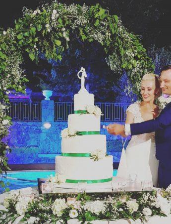 In questa foto due sposi tagliano la torta nuziale a quattro piani decorata con fiori bianchi e nastri colore Tiffany davanti ad un arco di foglie. Il bordo del tavolo è circondato di fiori bianchi e foglie